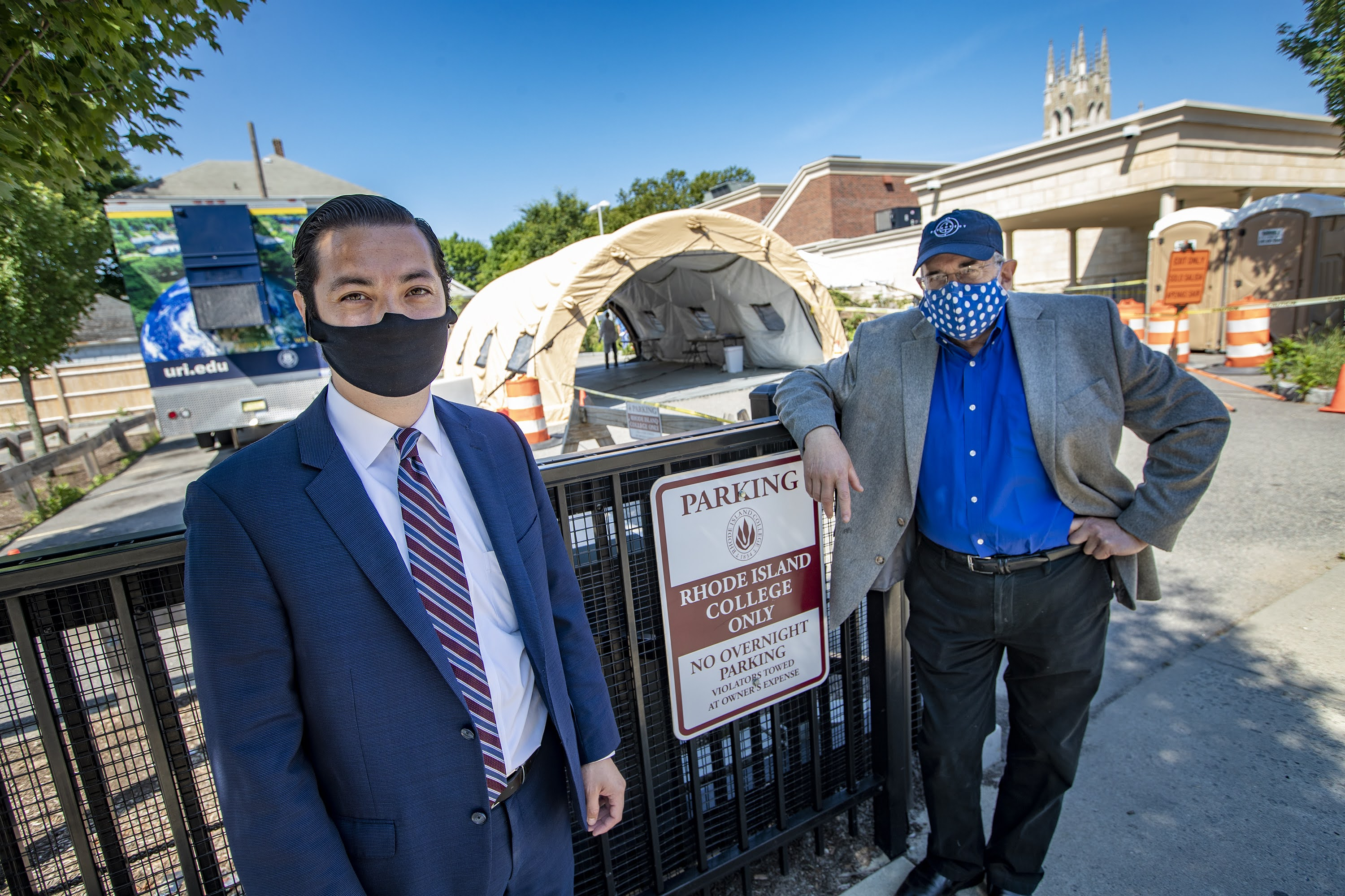 Central Falls Mayor James Diossa, left, and Dr. Michael Fine stand in front of the Rhode Island College walk-up testing site in Central Falls. (Jesse Costa/WBUR)