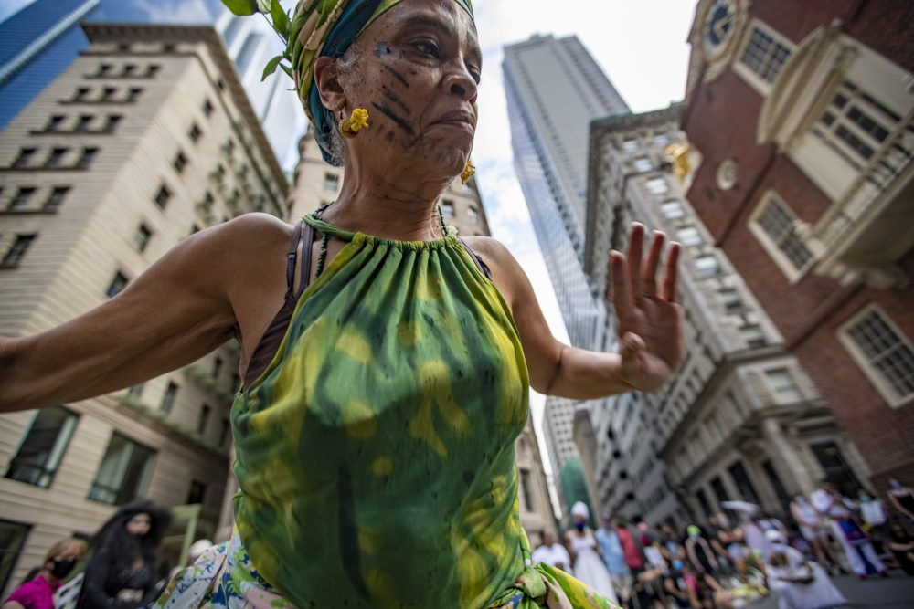 Isaura Oliveira dances around the marker at the site of the Boston Massacre, in front of the Old State House, during the Dismantle Now! BIPOC Solidarity Against White Supremacy demonstration. (Jesse Costa/WBUR)