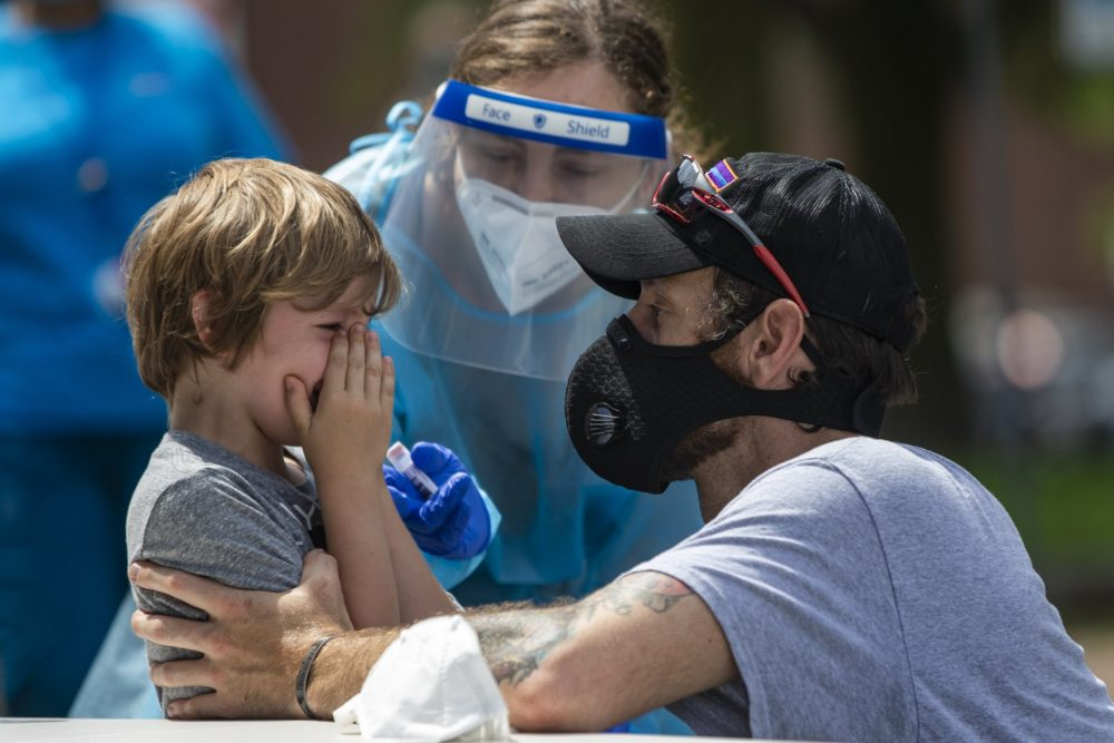 A young boy cries to his father after being tested for COVID-19 at the free testing being offered by the state in Chelsea Square. (Jesse Costa/WBUR)