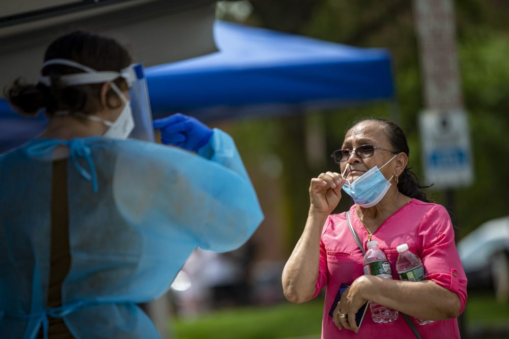 A Chelsea resident is being directed by a health care worker before inserting a swab up her nose during free COVID-19 testing offered by the state in Chelsea Square. (Jesse Costa/WBUR)