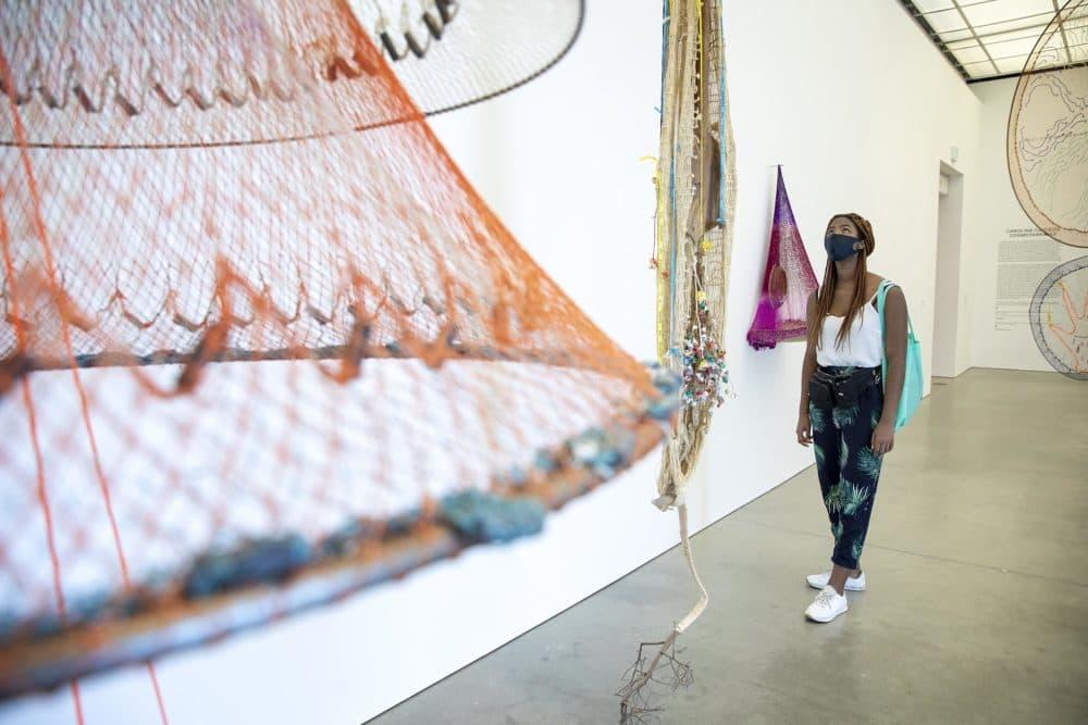 Jacarrea Garraway looks up at an installation in Carolina Caycedo's Cosmotarrayas exhibit at the ICA. (Robin Lubbock/WBUR)