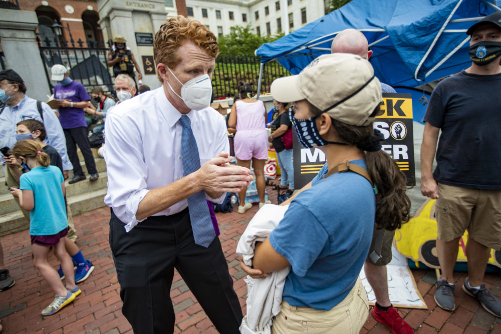 U.S. Rep. Joe Kennedy III speaks to a rally participant before the Strike for Black Lives. (Jesse Costa/WBUR)