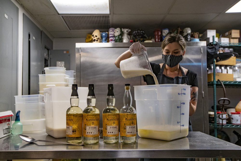 Brit McMahan, manager at Drink in Boston, pours coconut milk into a container of pineapple juice while preparing a batch of piña colada for take out. (Jesse Costa/WBUR)