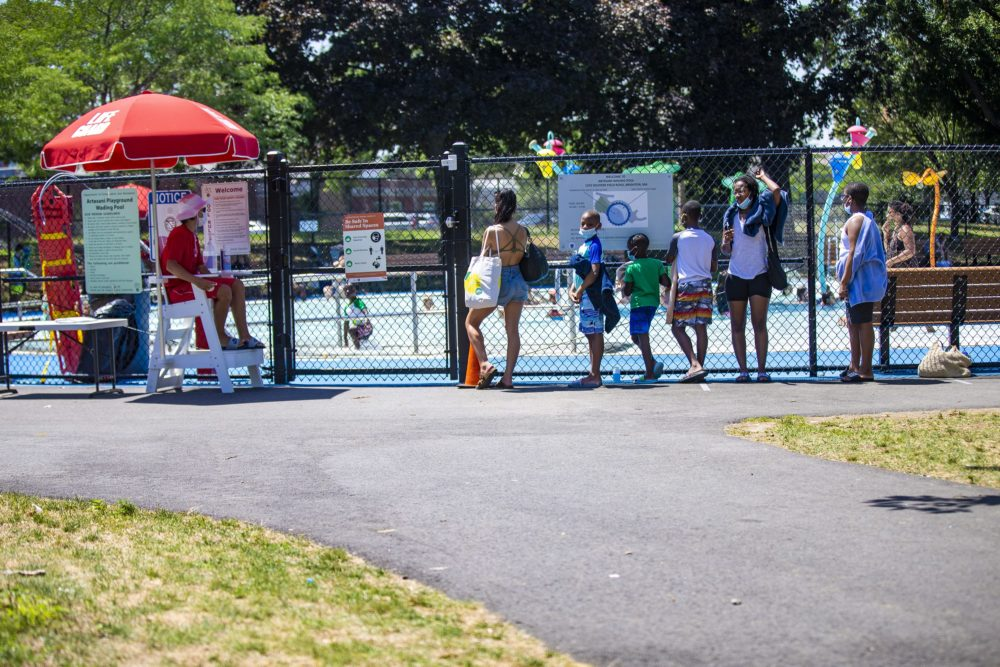 People wait in line to enter the pool at the Artesani Playgound in Allston. The pool is operating at 50% capacity. (Jesse Costa/WBUR)