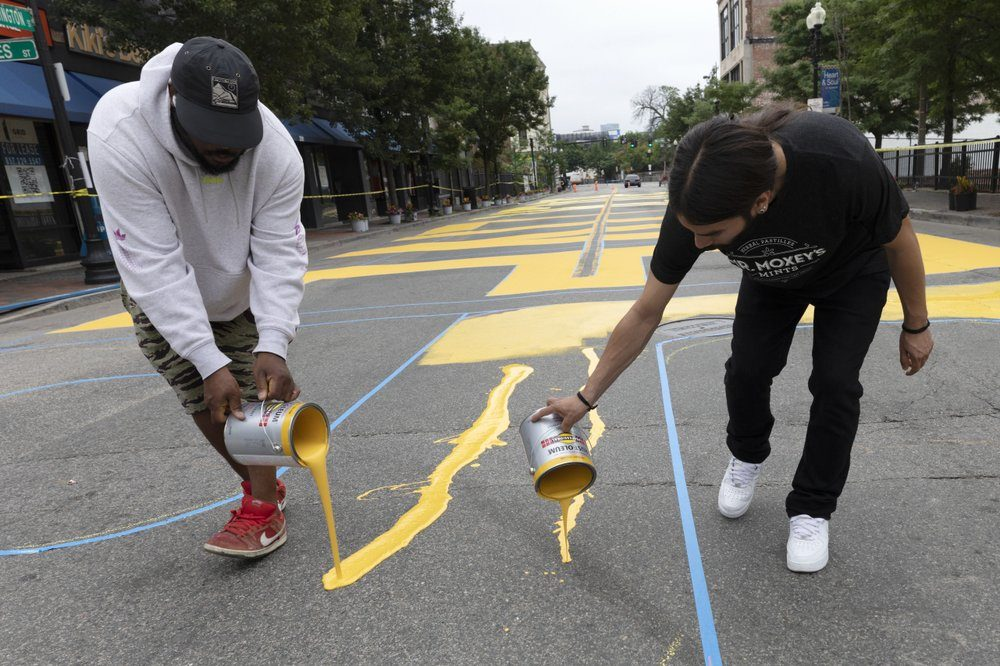 Lee Beard, left, and Mar paint the phrase Black Lives Matter on Washington Street, Sunday, July 5, 2020, in Roxbury. (Michael Dwyer/AP Photo)