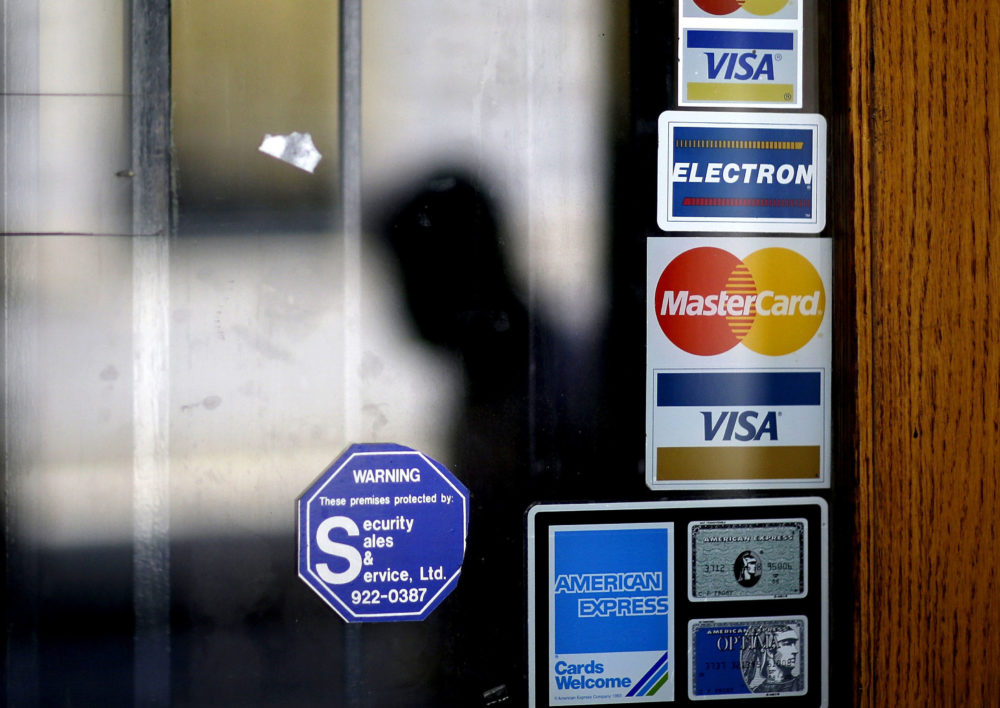 In this 2012 file photo, a pedestrian walks past credit card logos posted on a downtown storefront in Atlanta. (David Goldman/AP)