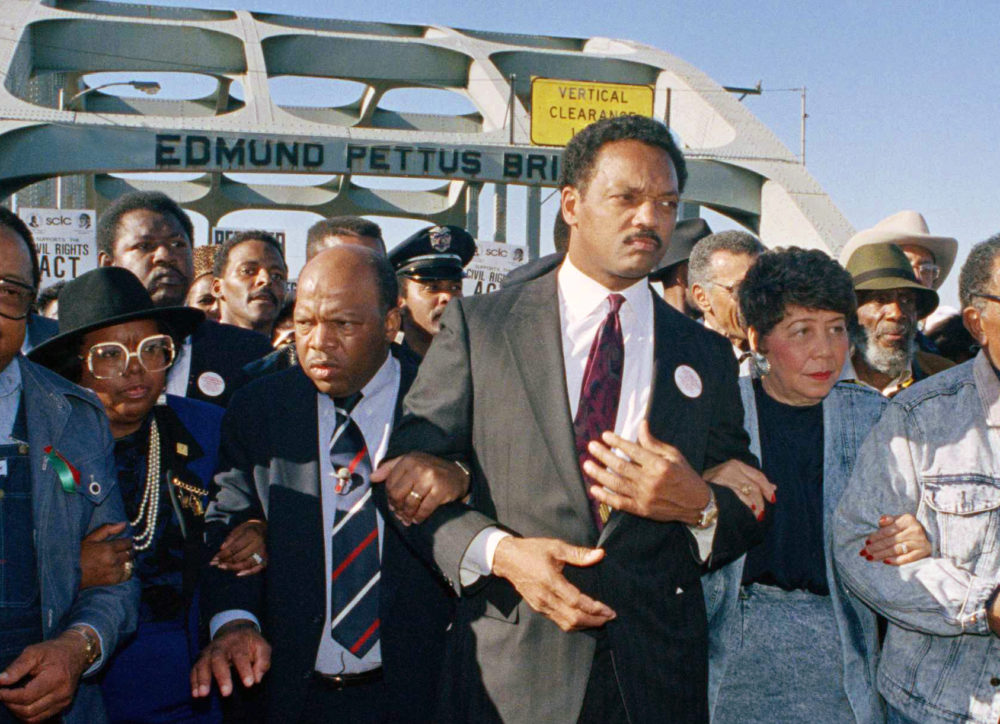 In this March 4, 1990 file photo, civil rights figures lead marchers across the Edmund Pettus Bridge during the recreation of the 1965 Selma to Montgomery march in Selma, Ala. From left are Hosea Williams of Atlanta, Georgia Congressman John Lewis, Rev. Jesse Jackson, Evelyn Lowery, SCLC President Joseph Lowery and Coretta Scott King. (Jamie Sturtevant/AP Photo)