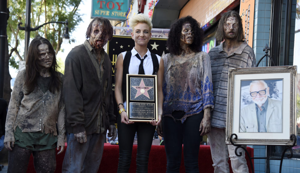 "Tina Romero, center, daughter of the late director George A. Romero, poses with zombie characters following a ceremony honoring him with a star on the Hollywood Walk of Fame on Wednesday, Oct. 25, 2017, in Los Angeles. Romero, the writer/director of the 1968 film ""Night of the Living Dead"" died on July 16. (Photo by Chris Pizzello/Invision/AP)"