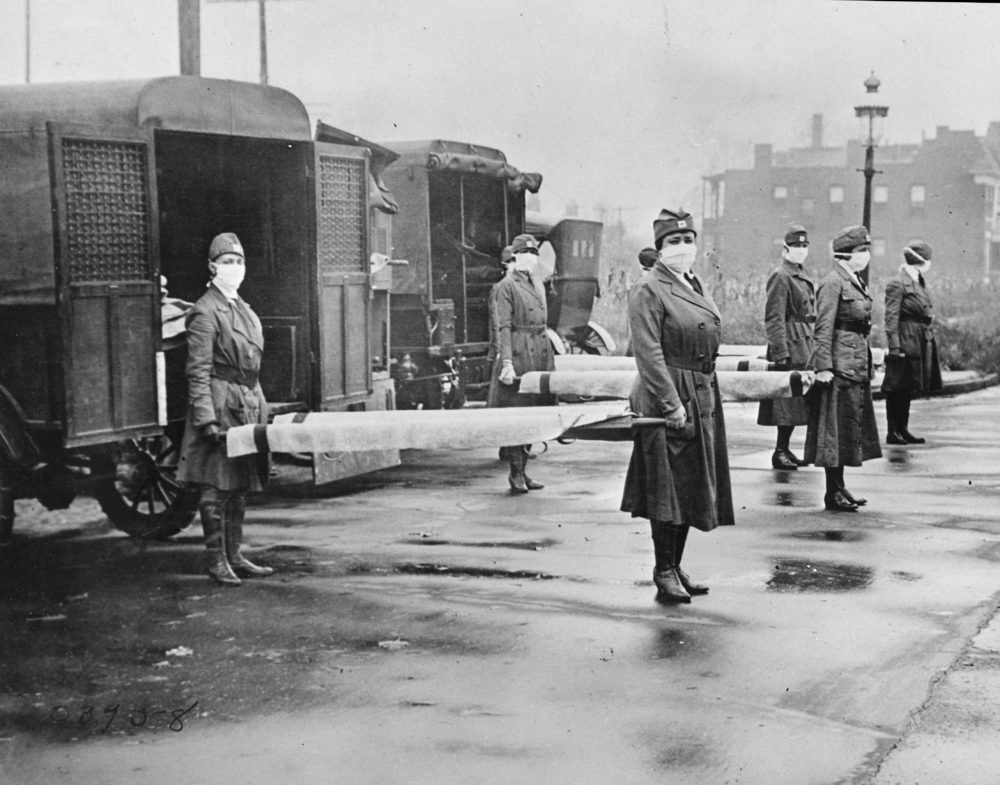 In this October 1918 photo made available by the Library of Congress, St. Louis Red Cross Motor Corps personnel wear masks as they hold stretchers next to ambulances in preparation for victims of the influenza epidemic. (Library of Congress via AP)