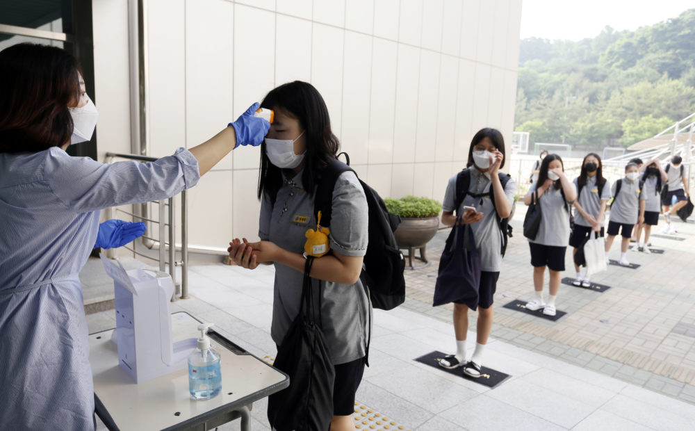Students wearing face masks to help protect against the spread of the novel coronavirus stand in a line to have their body temperatures checked before entering their classrooms at a middle school in Chungju, South Korea, Monday, June 8, 2020. (In Jin-hyun/Newsis via AP)