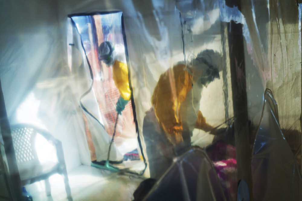 In this July 13, 2019 file photo, health workers wearing protective suits tend to an Ebola victim kept in an isolation tent in Beni, Congo. (Jerome Delay/AP)