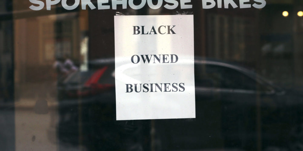 In this June 24, 2020, photograph, a sign in the window informs passersby that Spokehouse Bikes in the Upham's Corner neighborhood of Boston is a Black-owned business. (Charles Krupa/AP)