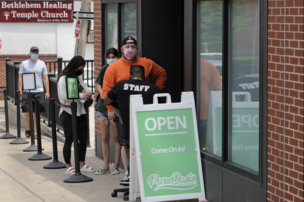 In this June 24, 2020, photograph, customers wait in line at Pure Oasis, a Black-owned recreational marijuana dispensary, in the Grove Hall neighborhood of Boston. Many from outside Boston have recently shopped and supported the store which was robbed and vandalized earlier in the month. (Charles Krupa/AP)
