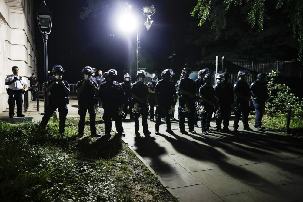 Police officers stand guard at City Hall as protesters gather near an encampment outside, Tuesday, June 30, 2020, in New York. (John Minchillo/AP)