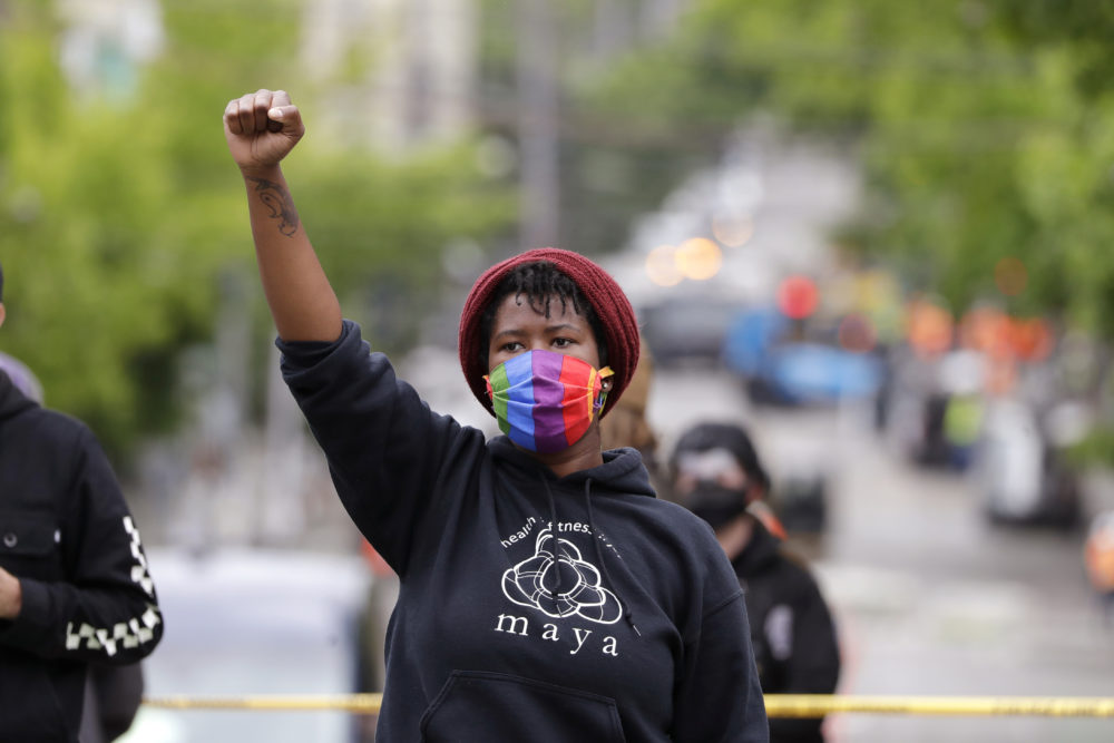 Demonstrator Elisha Ewing raises a fist as she stands during a protest Wednesday, July 1, 2020, in Seattle, where streets had been blocked off in an area demonstrators had occupied for weeks. (Elaine Thompson/AP)