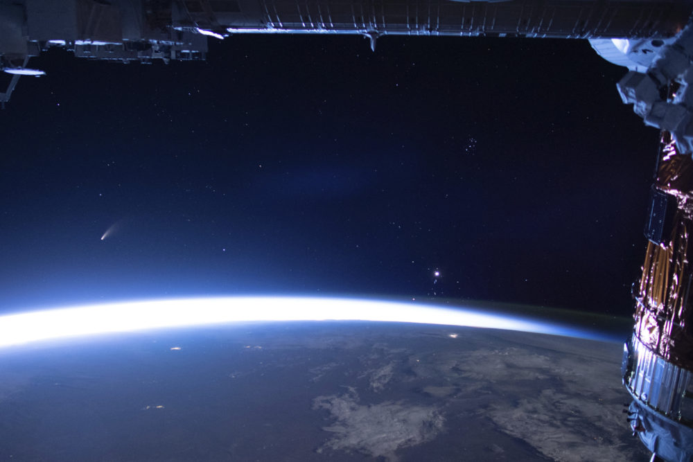Comet Neowise, left, is seen in the eastern horizon above Earth in this image taken from the International Space Station on Sunday, July 5, 2020. (NASA via AP)