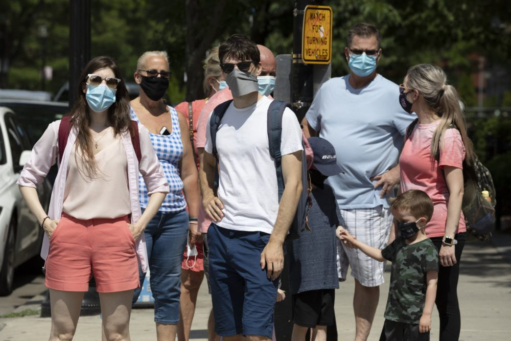 People wearing protective masks stand on the corner during a busy day on Newbury Street, July 11, 2020, in Boston. (Michael Dwyer/AP)