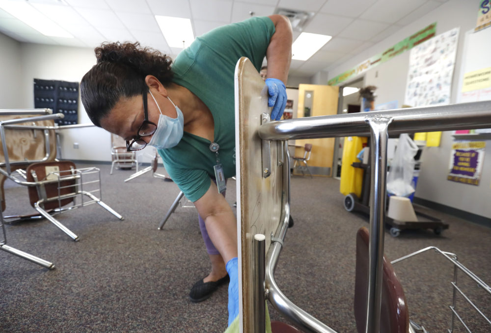 Josefina Median wears a mask as she cleans a classroom at Wylie High School Tuesday, July 14, 2020, in Wylie, Texas. (LM Otero/AP)