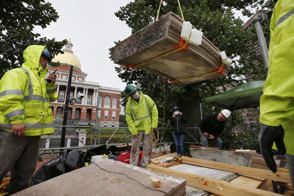 "Workers inspect the top cornice stone as it is lifted from the Shaw 54th Regiment memorial opposite the State House, July 17, 2020, in Boston. Amid the national reckoning on racism, the memorial to the first Black regiment of the Union Army, the Civil War unit popularized in the movie ""Glory,"" is facing scrutiny.(Michael Dwyer/AP)"