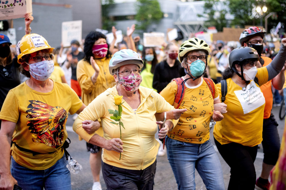 "Norma Lewis holds a flower while forming a ""wall of moms"" during a Black Lives Matter protest on Monday, July 20, 2020, in Portland, Ore. (Noah Berger/AP)"