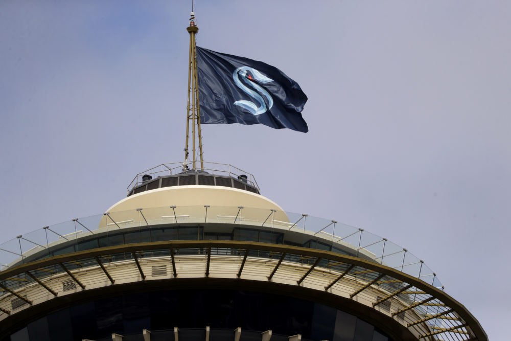 A flag with the new logo for the newly-named Seattle NHL team, the Seattle Kraken, flies atop the Space Needle. (Elaine Thompson/AP)