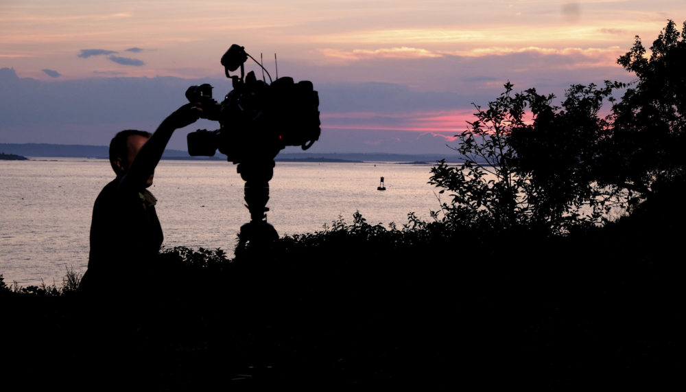 A member of a TV crew adjusts their camera while filming near the shore of Bailey Island, Maine, where a woman swimming off the coast was killed in an apparent shark attack July 27, 2020. Two kayakers helped the person get to shore, and an ambulance provided further assistance, but she was pronounced dead at the scene, Marine Patrol said. (Jim Gerberich/AP)