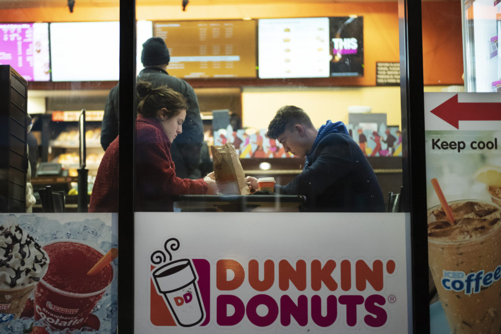 In this Jan. 30, 2019 photo, customers sit inside a Dunkin' Donuts in New York. (Mark Lennihan/AP)