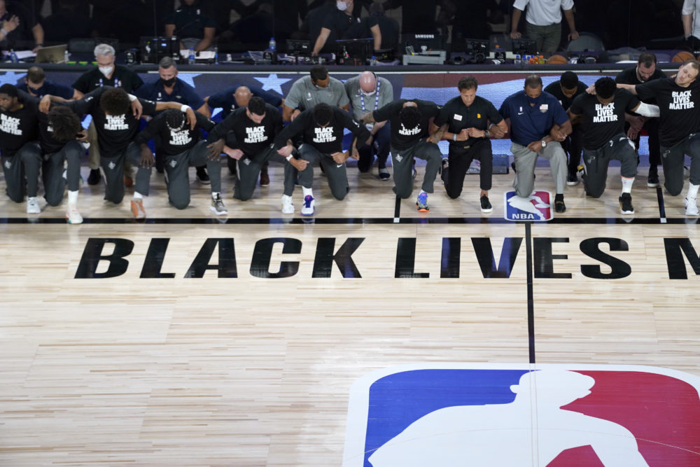 Members of the Pelicans and Jazz kneel together during the national anthem before their game on Thursday. (Ashley Landis/AP)