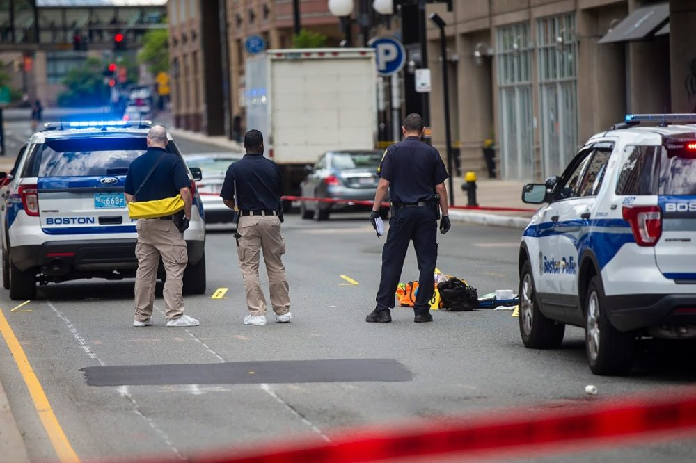 Boston Police examine the evidence on the ground in front of the Colonnade Hotel on Huntington Ave. following a shooting that claimed the life of Boston taxi driver Luckinson Oruma in June, 2019. (Jesse Costa/WBUR)