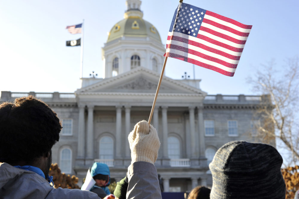 A man waves a U.S. flag outside the New Hampshire State House. (Joseph Prezioso/AFP via Getty Images)