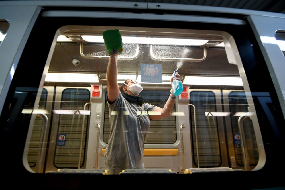 A cleaner wearing gloves and a protective face mask disinfects and cleans a metro train. (Damien Meyer/AFP via Getty Images)