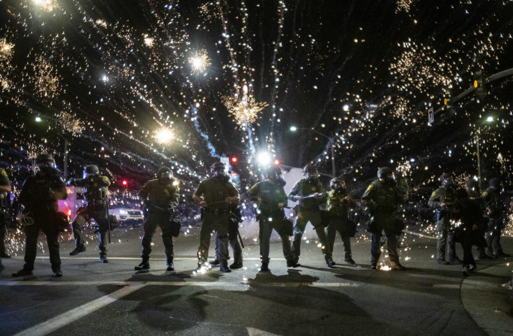 Orange County Sheriff deputies maintain a police block as a firecracker thrown by a protester explodes behind them during a protest against the Minneapolis police killing of George Floyd during the coronavirus pandemic on May 30, 2020 in Santa Ana, California. (Gina Ferazzi / Los Angeles Times via Getty Images)