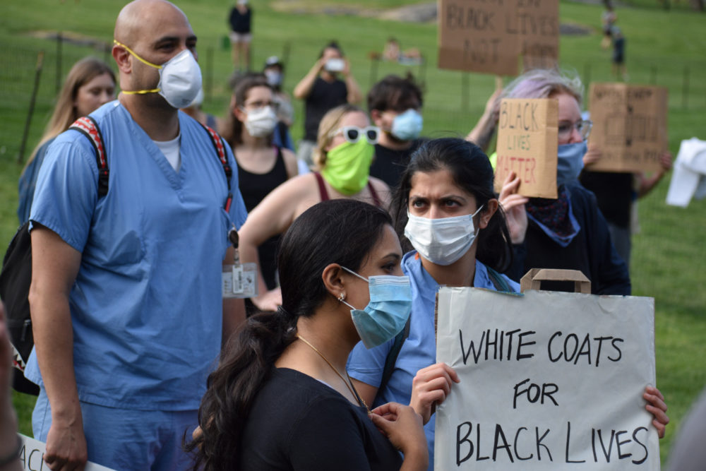 Medical workers in face masks hold signs during a rally organized by a group named White Coats for Black Lives in Central Park on June 6, 2020. (Maria Khrenova/Getty Images)