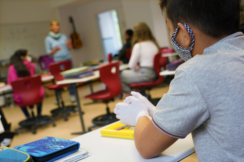 A sixth grader wears a protective face mask and gloves as he attends class for the first time since March at the GutsMuths Grundschule elementary school during the novel coronavirus crisis on May 4, 2020 in Berlin, Germany. (Sean Gallup/Getty Images)