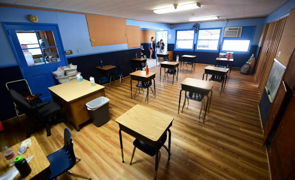 Children in an elementary school class wearing masks enter the classroom with desks spaced apart as per coronavirus guidelines during summer school sessions in Monterey Park, California. (Frederic J. Brown/AFP/Getty Images)