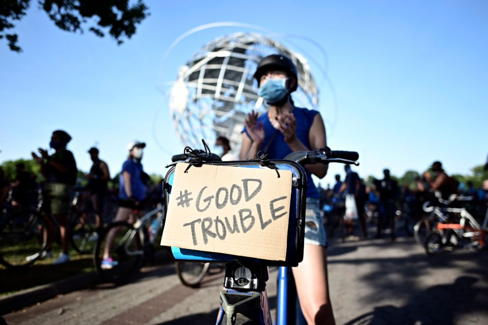 A protestor displays a sign that read #Good Trouble, in homage to recently deceased Congressman and activist John Lewis during a Justice Ride, supporting the Black Lives Matter movement on July 18, 2020 in the Flushing Meadows-Corona Park in the borough of Queens, New York City. (Johannes Eisele/AFP)