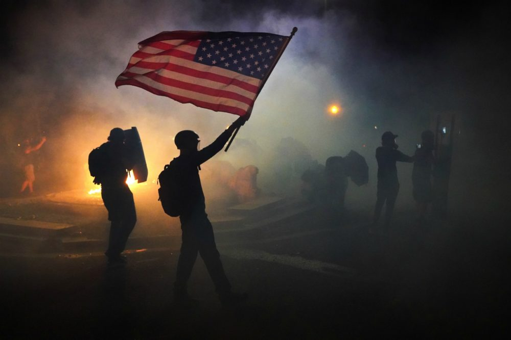 A protester flies an American flag while walking through tear gas fired by federal officers during a protest in front of the Mark O. Hatfield U.S. Courthouse on July 21, 2020 in Portland, Ore. The federal police response to the ongoing protests against racial inequality has been criticized by city and state elected officials. (Nathan Howard/Getty Images)