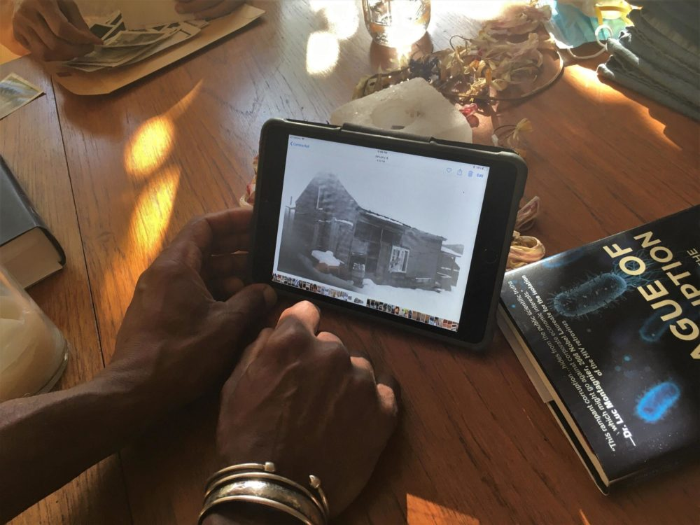 Gamal Buhaina holds an image of the original farmhouse belonging to his grandparents, John and Amelie Bates. (Anna Van Dine/VPR)