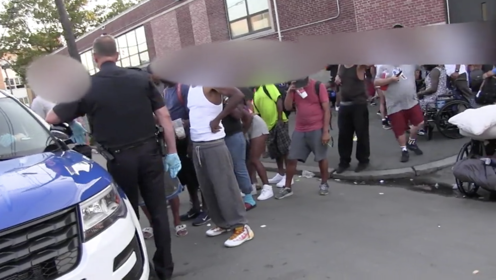"""People lined up outside a Boston police cruiser prepare to hand over their IDs so police can run them through the warrant check system during last year's """"Operation Clean Sweep."""" (Boston police footage courtesy ACLU)"""