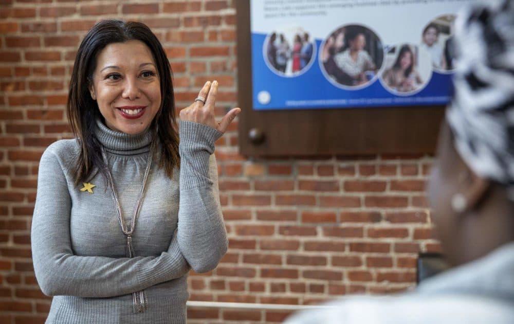 Malia Lazu, Berkshire Bank's regional vice for Eastern Massachusetts, talks with a visitor at Reevx Labs coworking space in Roxbury. (Robin Lubbock/WBUR)