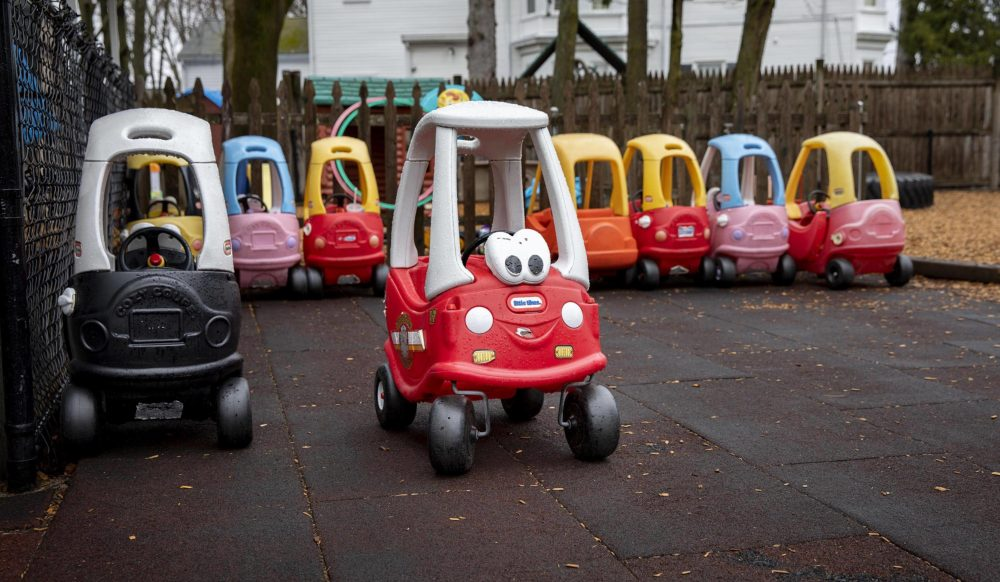 Children's vehicles parked at Waltham Day Care Center in March as providers closed as a precaution against the spread of COVID-19. (Robin Lubbock/WBUR)