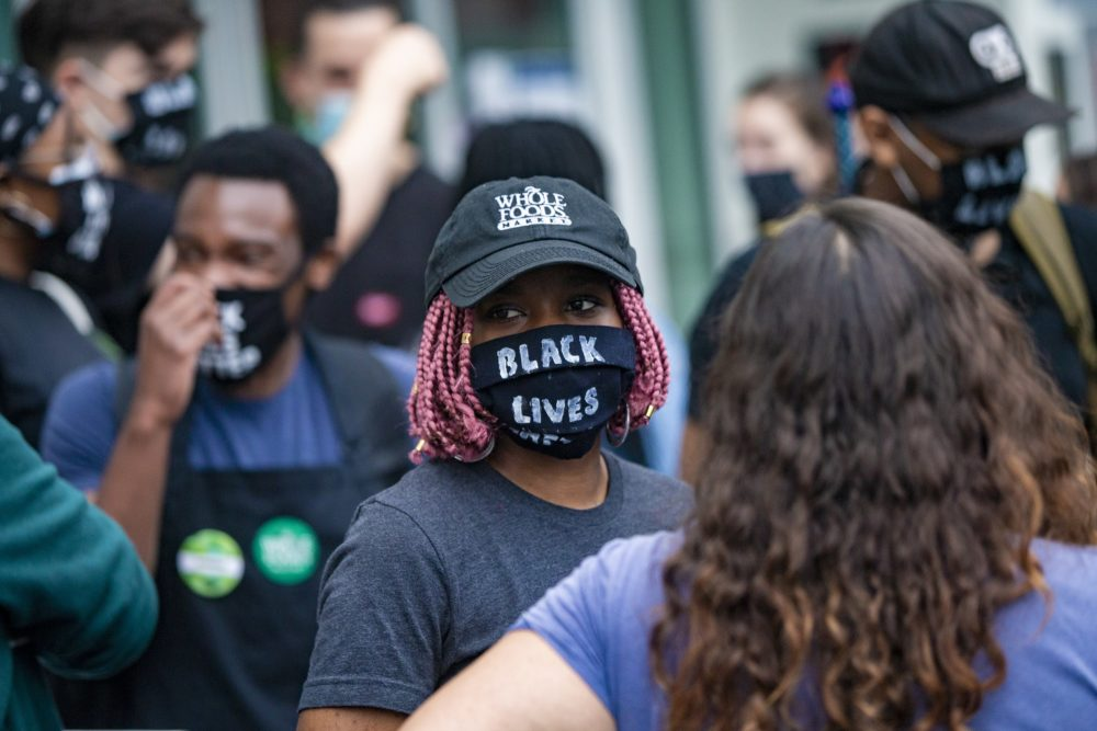 A group of Whole Foods employees dismissed by managers for wearing Black Lives Matter masks during their shifts gather outside of the Whole Foods on River Street in Cambridge in July 2020. (Jesse Costa/WBUR)