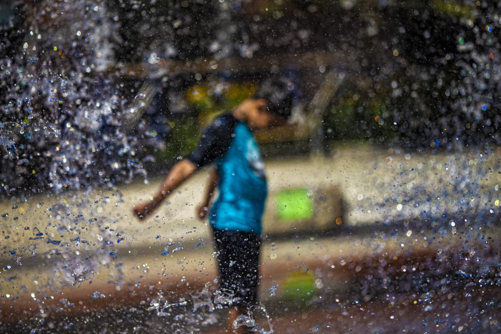A boy cools off in a fountain on the Rose Kennedy Greenway in Boston earlier this summer. (Jesse Costa/WBUR)
