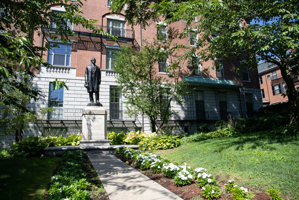 A statue of former U.S. Senate Majority Leader Henry Cabot Lodge stands on the State House west lawn, the site of his now-demolished boyhood home. Rising behind Lodge is 25 Beacon St., former headquarters of the Unitarian Universalist Association. (Sam Doran/SHNS)