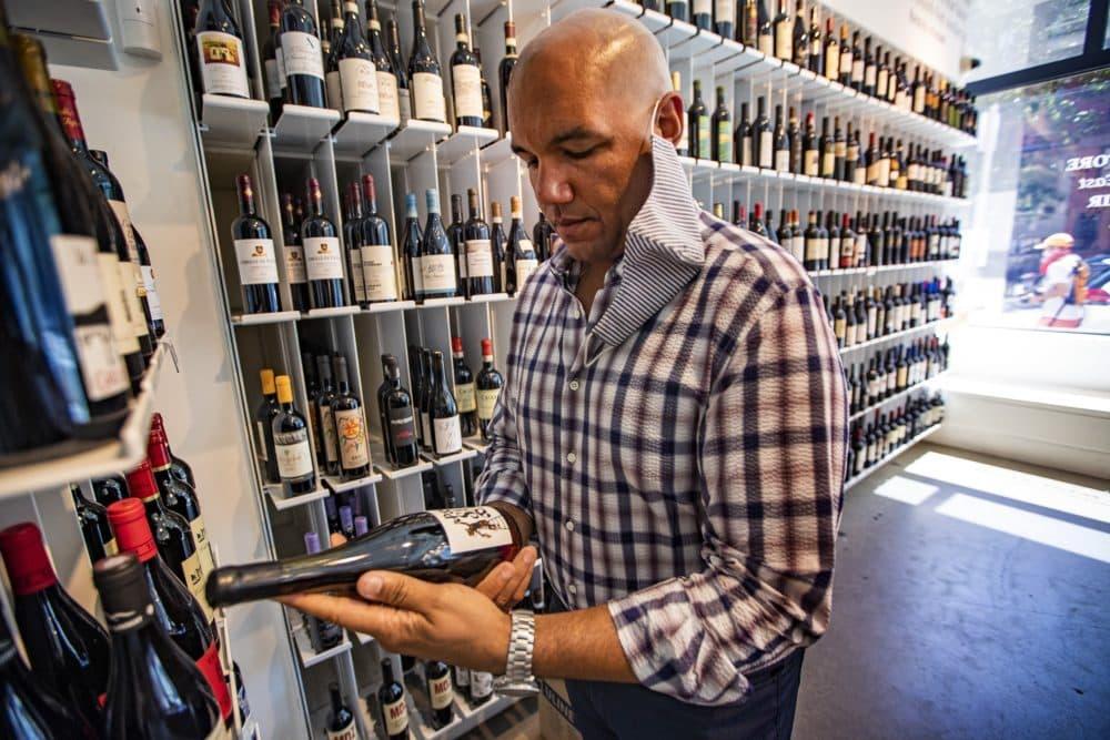 Urban Grape owner TJ Douglas examines a bottle of wine he's pulled off the shelf to taste. (Jesse Costa/WBUR)