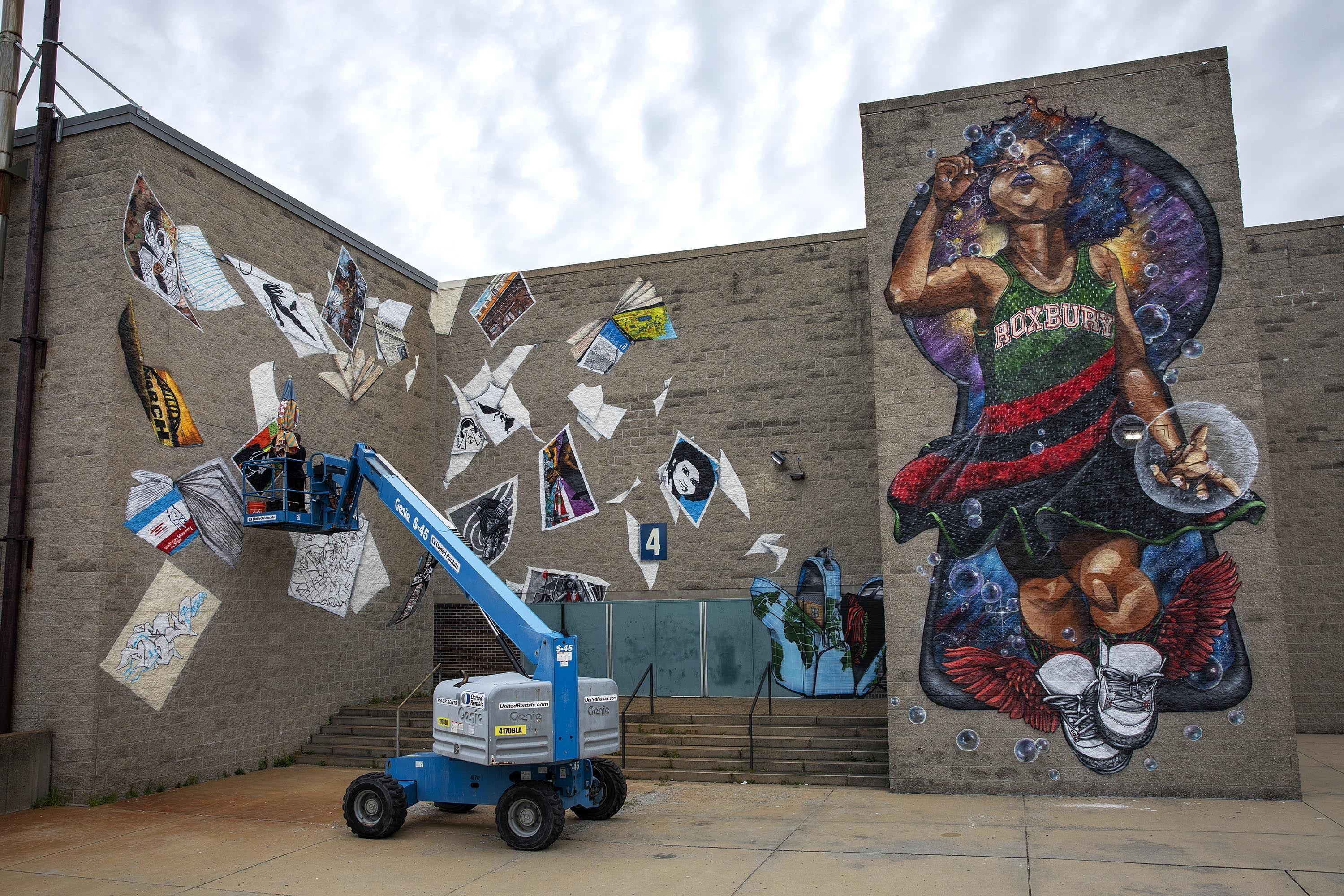 "Rob ""Problak"" Gibbs works on the third wall of the ""Breathe Life"" mural at Madison Park Technical Vocational High School, as the project nears completion. (Robin Lubbock/WBUR)"