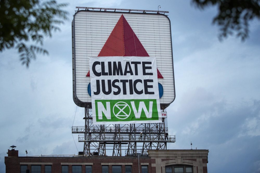 """Activists from Extinction Rebellion raised a banner on the side of the Citgo sign facing Fenway Park which read """"Climate Justice Now"""" on Monday evening. While the activists were still pulling up the sign the wind appeared to snap the bar holding the banner straight, causing it to collapse.. (Robin Lubbock/WBUR)"""