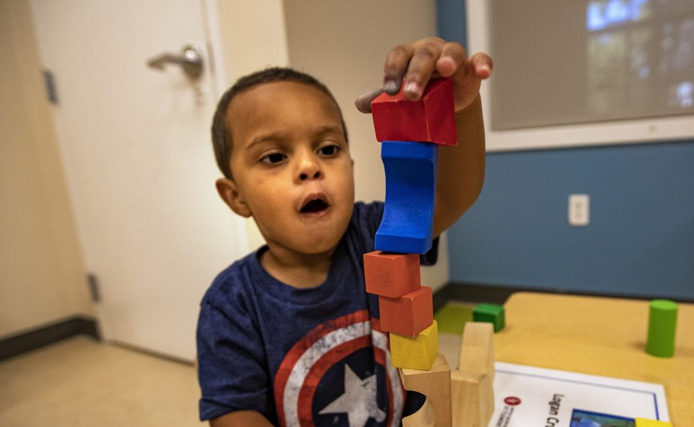 Children in the toddler room at the United South End Settlements summer program do activities such as building with blocks. (Jesse Costa/WBUR)