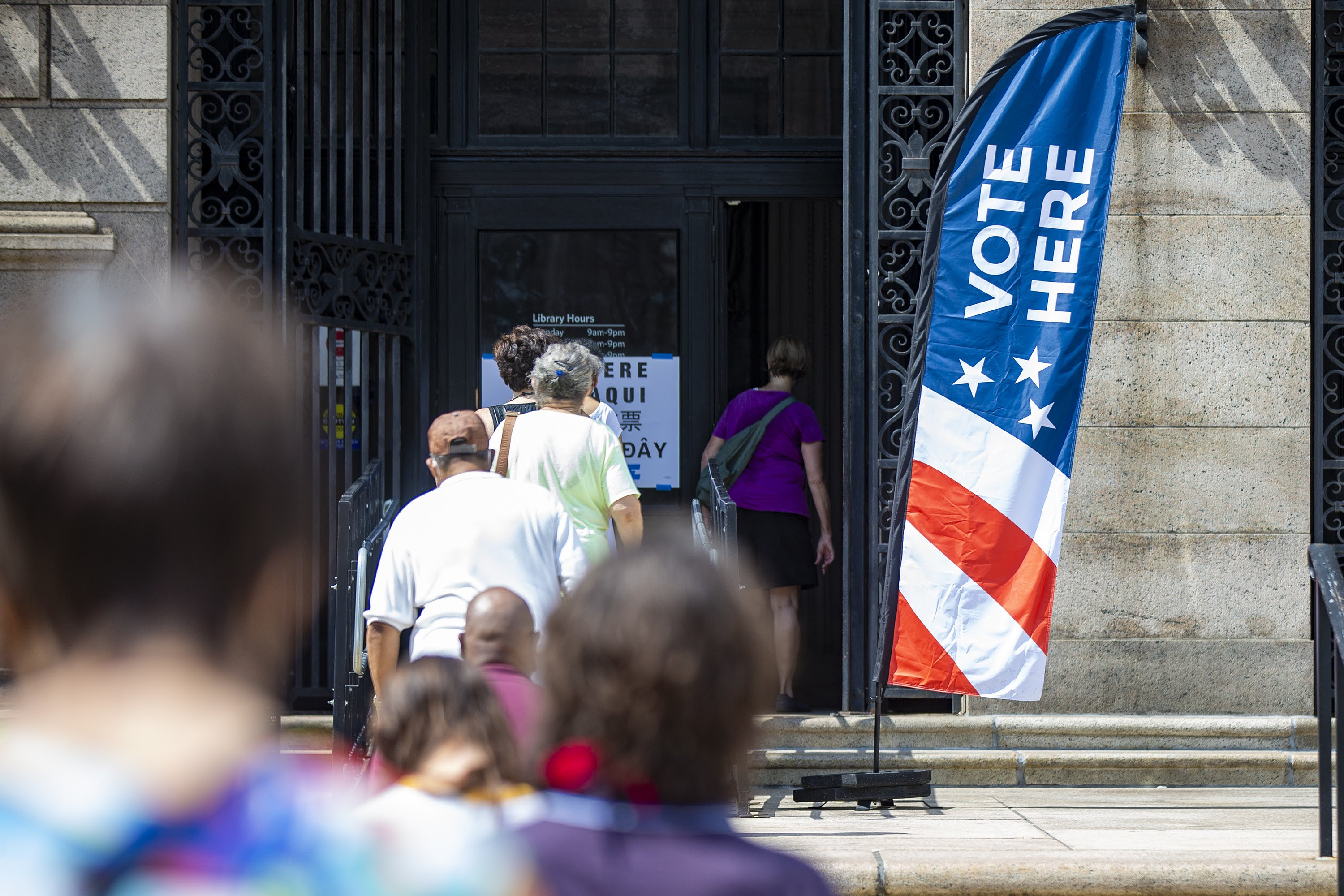 Voters stand in line six feet apart outside the Boston Public Library on the first day of early voting, Aug. 22, for the Massachusetts primary. (Jesse Costa/WBUR)