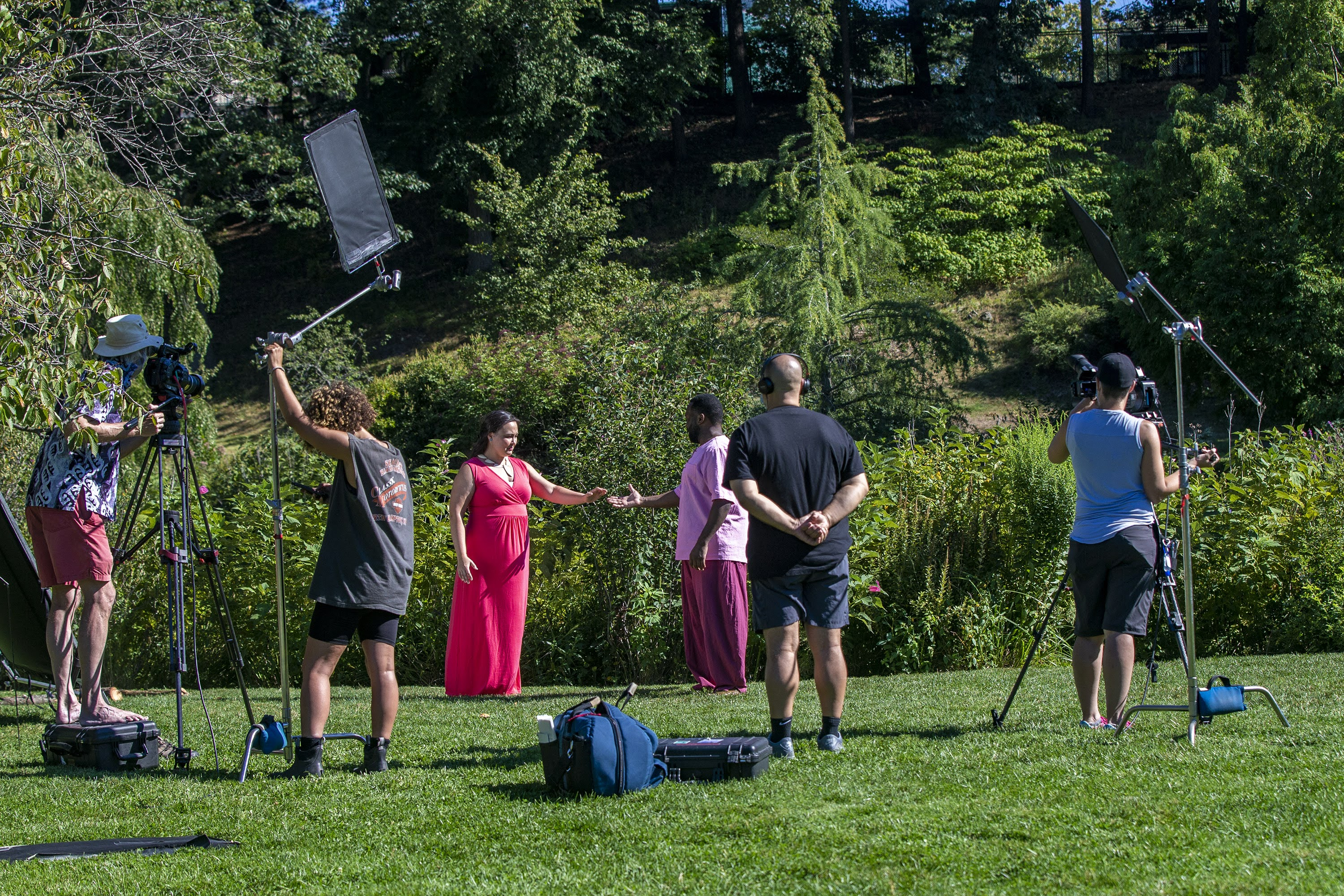 """Cast and crew filming the log scene of """"The Tempest"""" at the Arnold Arboretum, one of a series of selected scenes, sonnets and monologues by the Actors' Shakespeare Project called """"The Nature of Shakespeare."""" Each scene is being filmed and will be presented for online viewing in two episodes. (Jesse Costa/WBUR)"""